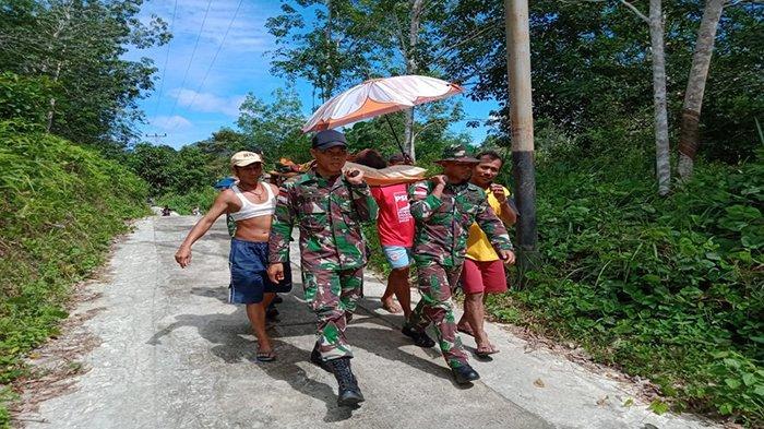 Akses Jalan Sulit Personel Satgas Yonmek 643 Tandu Warga yang Sakit Pulang ke Rumah