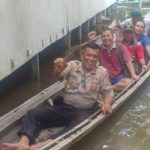 Dengan Perahu Kecil Kapolsek Batang Tarang Sambang ke Desa yang Terkena Banjir
