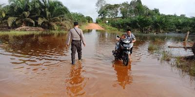 Bhabinkamtibmas Cek Jalan Masuk Dusun Sayu dan Dusun Sansat Desa Sansat yang Tergenang Banjir