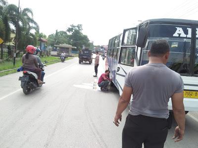 Anggota Polsek Parindu Membersihkan Minyak Mobil Bus ABM Yang Tumpah di Jalan Raya
