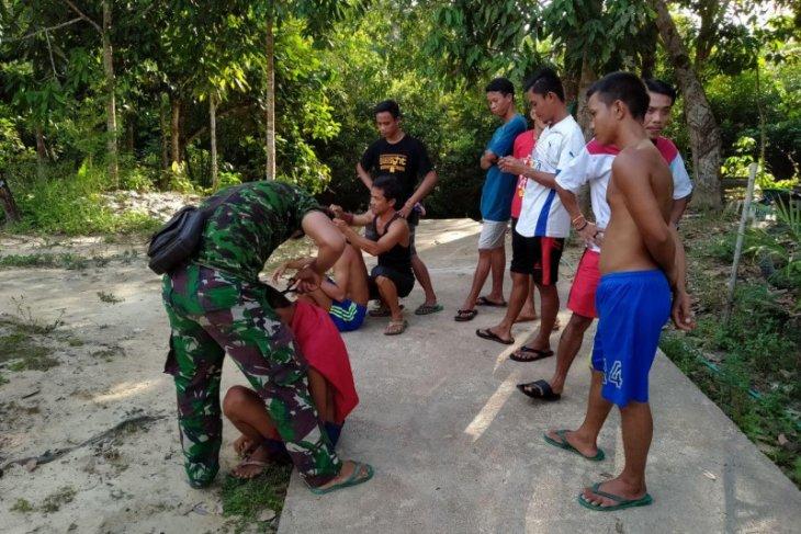 Pemuda Dusun Sekura, potong rambut gratis dengan prajurit TMMD
