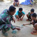 Manfaatkan waktu luang, prajurit TMMD bermain kelereng bersama anak-anak