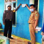 Bhabinkamtibmas Polsek Entikong Bersama Kepala Desa Tempelkan Imbauan untuk Tidak Mudik